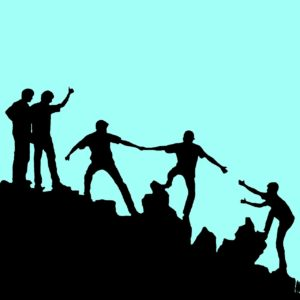 People helping each other up a mountain.