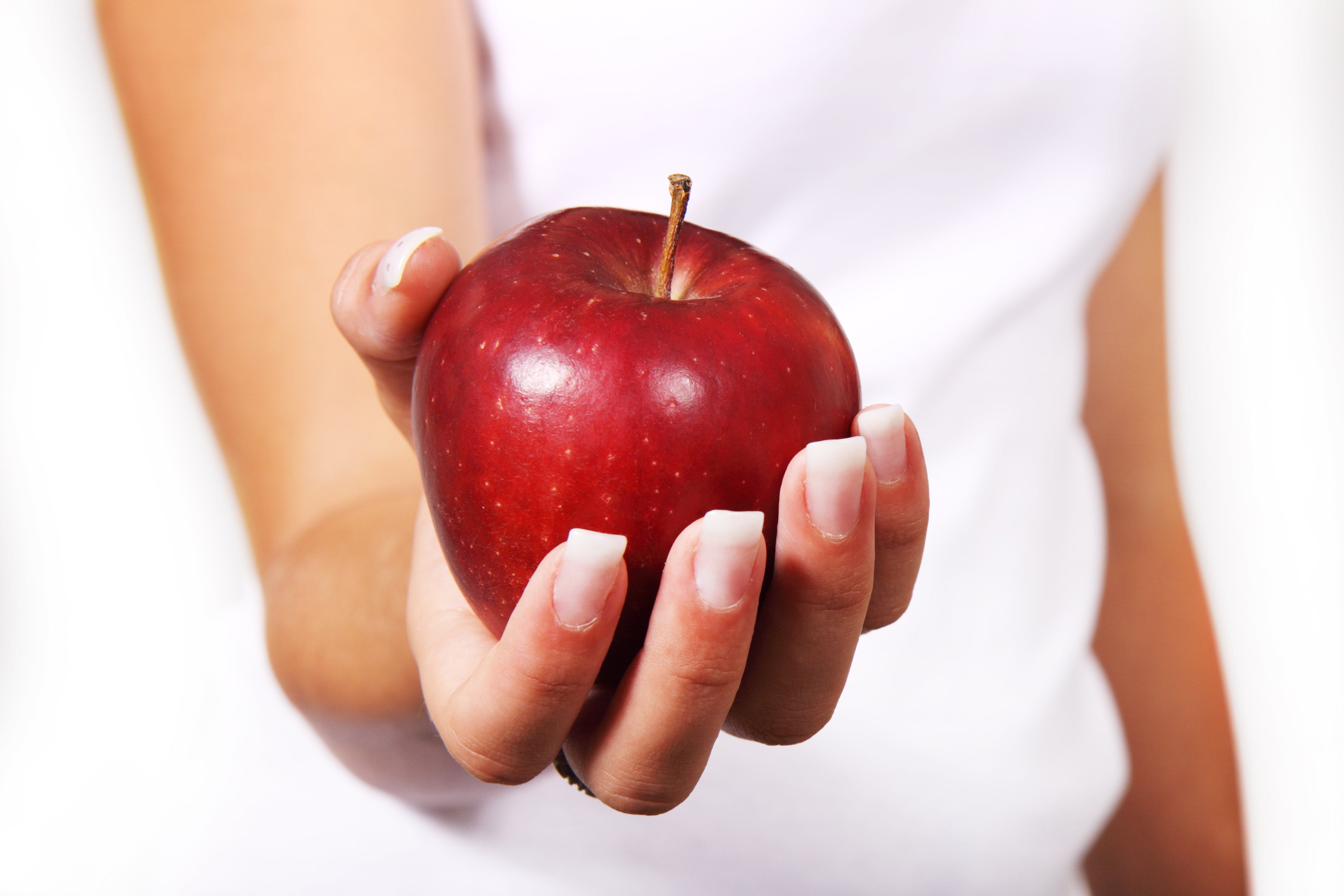 A red apple held in a woman's hand with her arm outstretched as if offering it to the viewer.