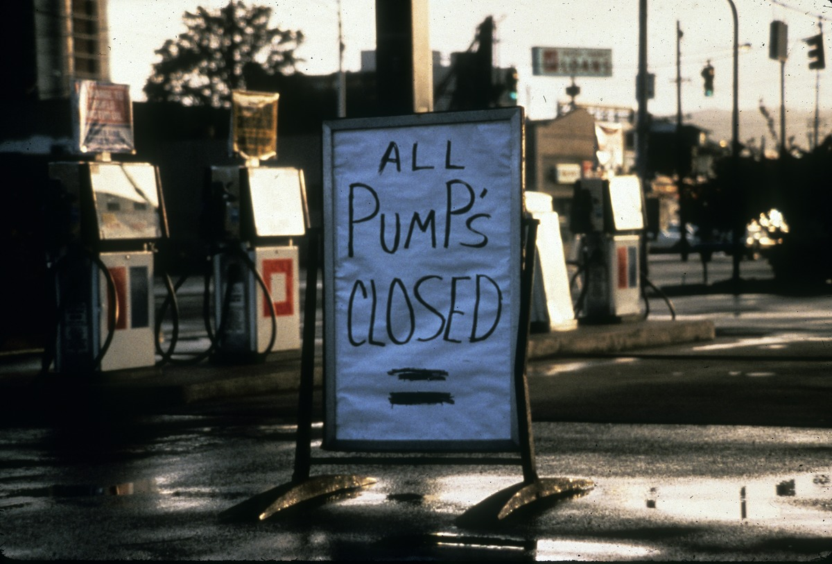 "Hand written sign in front of gas station saying ""All Pump's Closed"""