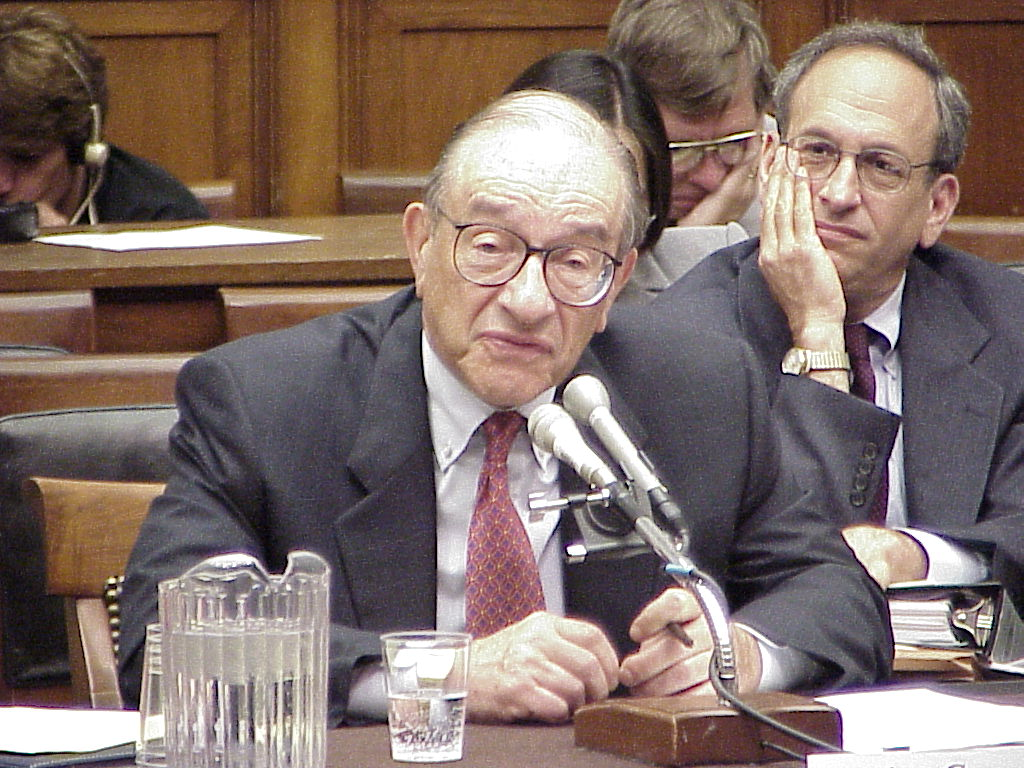 Alan Greenspan, seated at a table testifying before the House Financial Services Committee.