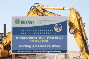 Construction equipment and a sign for the Recovery Act-funded work at the Hanford site.