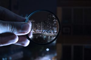 Magnifying glass showing a city scene through the glass.