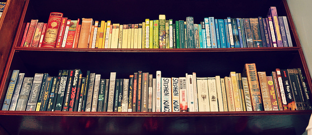 Two rows of a bookshelf where the spines are arranged by color