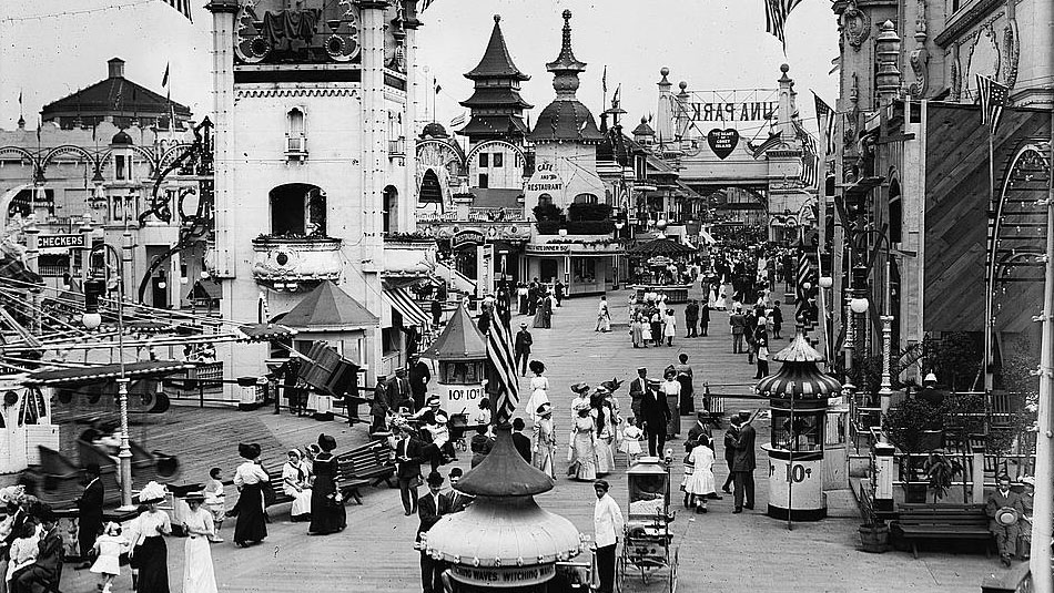Photograph of Luna Park on Coney Island showing decorative buildings , street vendors, and people.