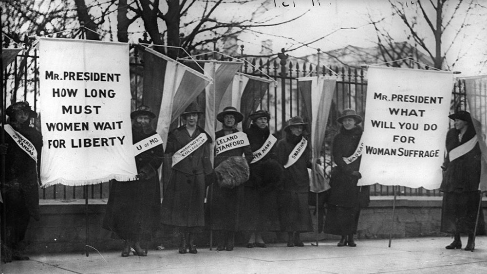 """Suffragettes picket with signs saying, """"Mr. President how log must women wait for liberty?"""" and """"Mr. President what will you do for woman suffrage?"""""""