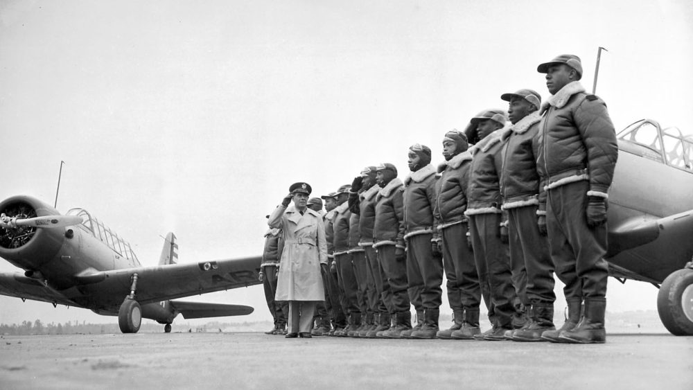 Tuskege Airmen (African-American pilots) stand at attention in front of their aircraft.