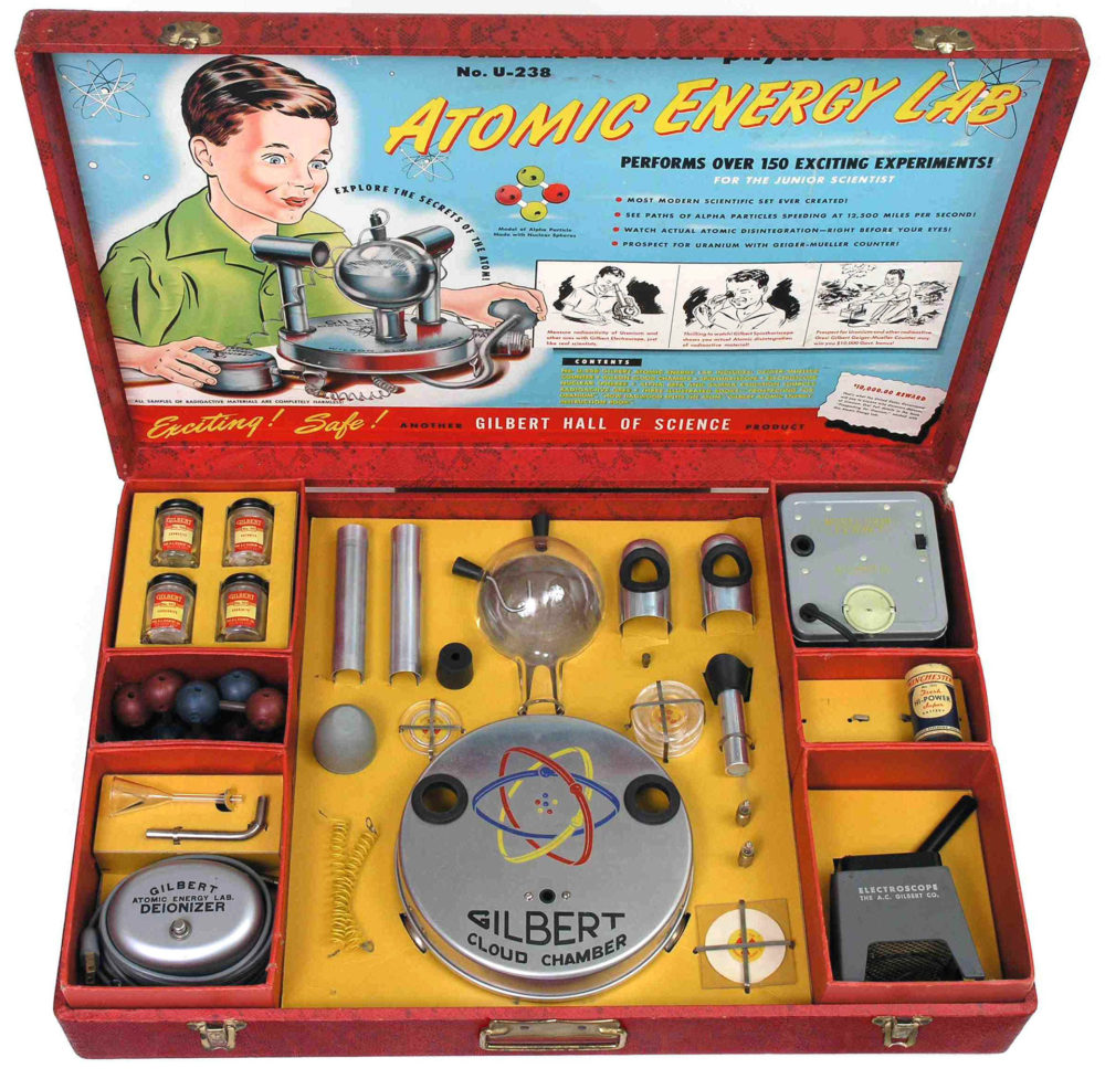 Atomic Energy Lab kit, packaged in a red briefcase with a boy excitedly playing with the pieces in a picture on one side of the case, while the other is filled with the needed parts.