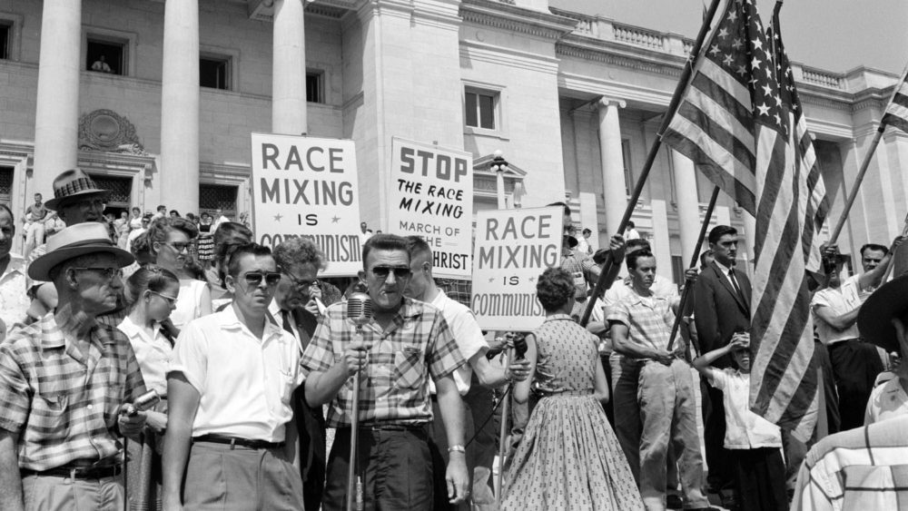 "White protesters outside of the Arkansas Capitol holding signs like ""mixing race is communism"" and American flags."