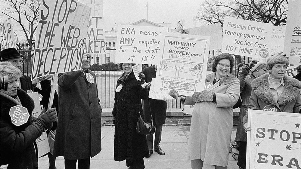 """Protestors against the ERA carry signs like """"stop the web of deception"""" and """"ERA means AMY register for the draft at 18"""" and """"Rosalyn Carter--tear up your own Soc Sec Card, not mine!"""""""
