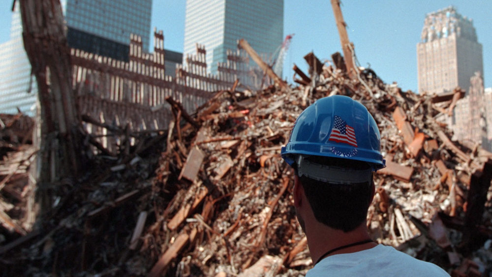 The back of a man's head in a construction hat (with an American flag log) who looks into the massive pile of rubble from the 9/11 attacks.