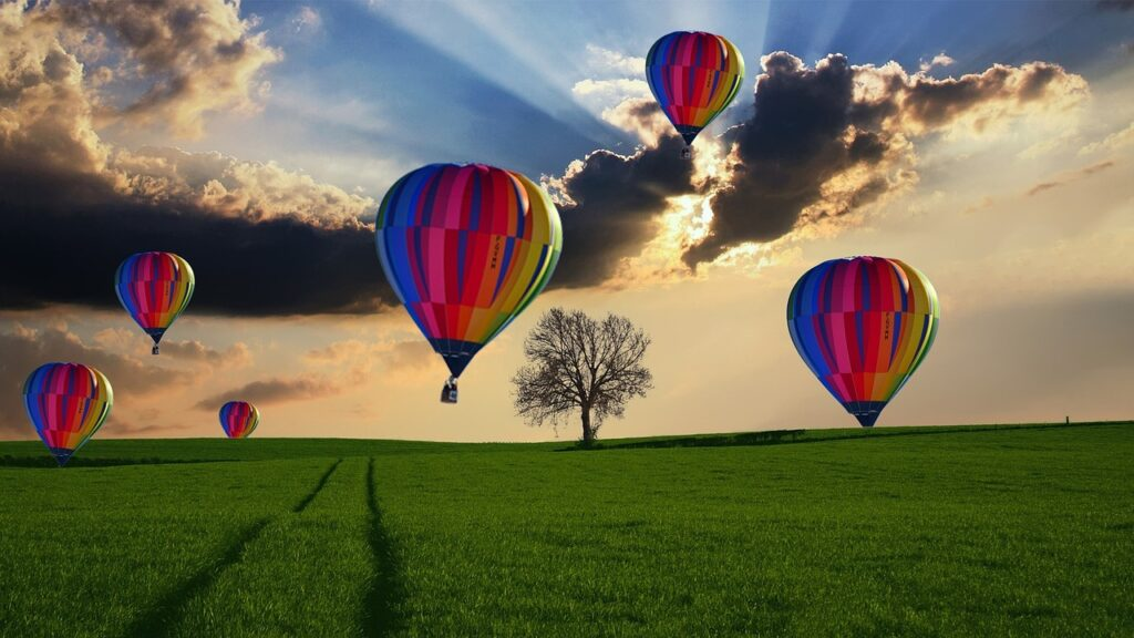Image of six rainbow colored hot air balloons at various heights over a field of green grass in a cloudy sunlit sky.