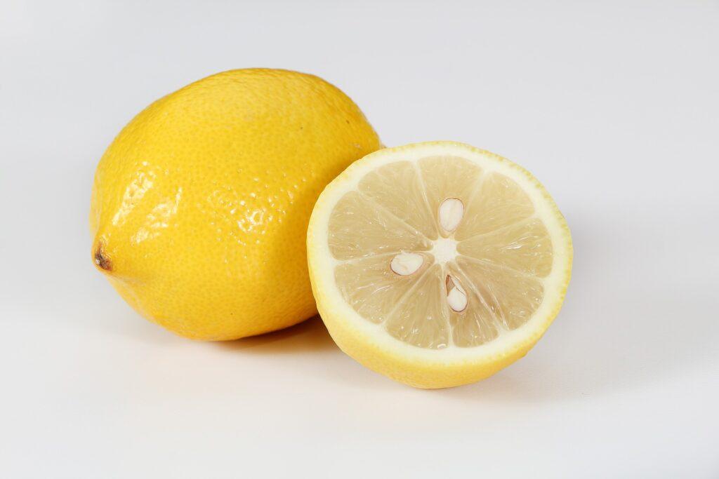 A yellow lemon next to a lemon half