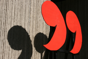 Photo of quotation mark sculpture. The punctuation marks are bright red, standing upright on thin rods. They cast dark shadows on the stone wall behind them