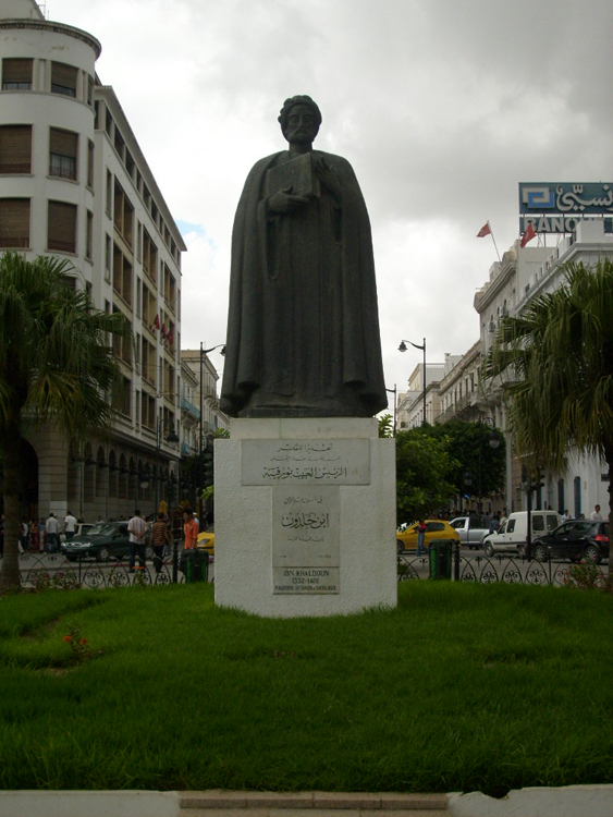 Figure (c) shows a statue of a man.