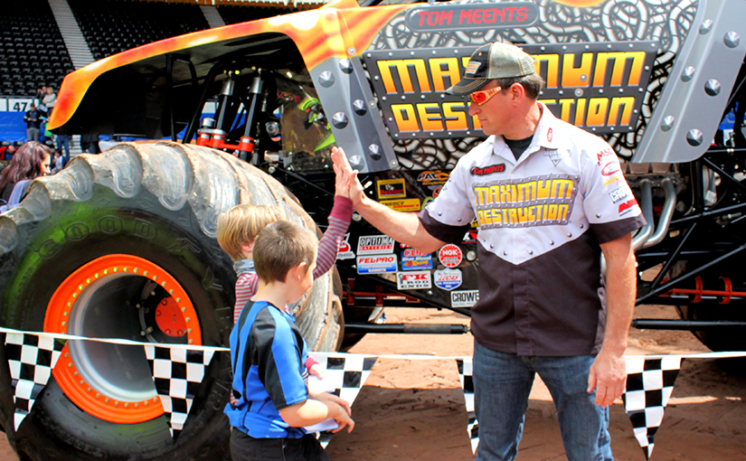 Photo of a monster truck driver giving a high five to a young boy