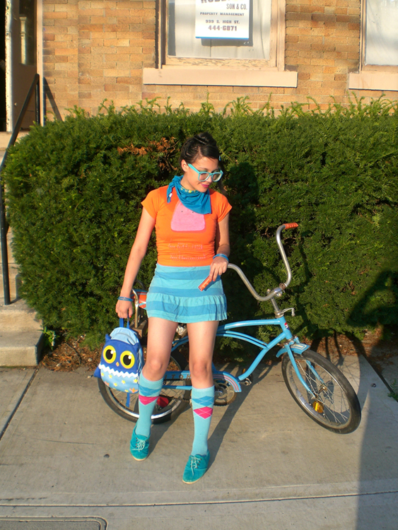 A young woman in brightly colored clothes and carrying an owl handbag is shown standing in front of a vintage blue bicycle, a large hedge, and a town house.