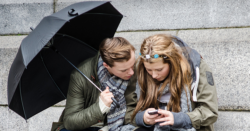 Photo of a teenage girl and guy looking at a cell phone
