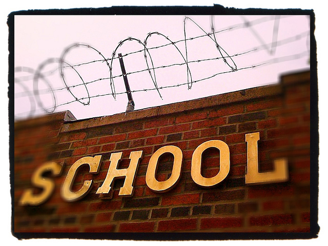 "A brick wall is shown with the word ""school"" on it and barbed wire on top."