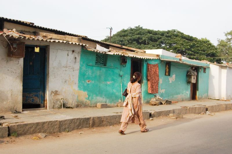 A woman in India is shown from behind walking down the street.