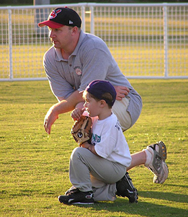 This image is of a kneeling man with a small child who is learning to play baseball.