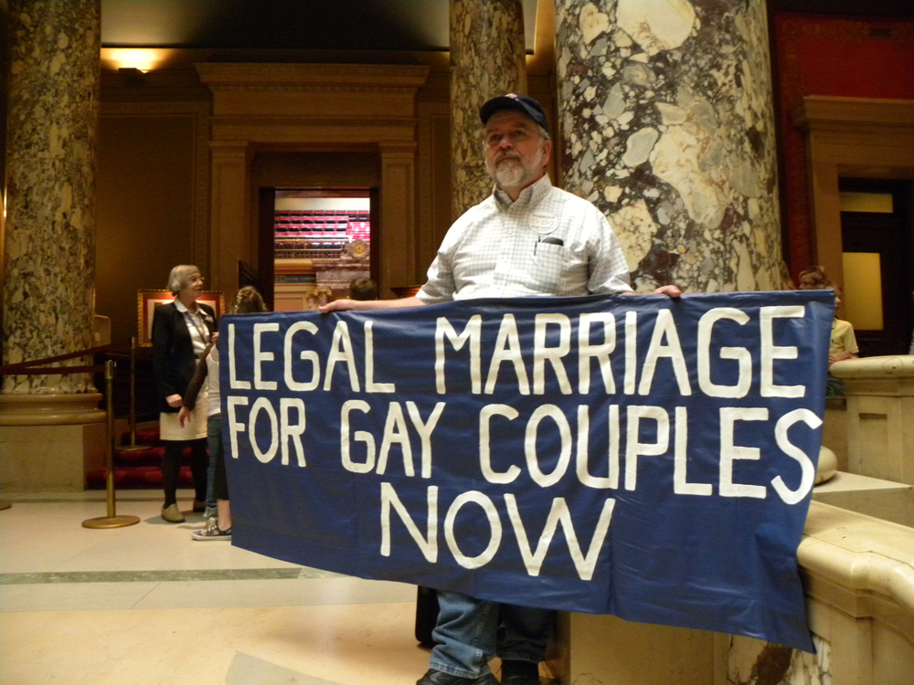 """An older man with a gray beard, wearing a baseball cap, buttoned-up shirt, and jeans, is shown in a marbled lobby with columns holding a blue banner reading """"Legal Marriage for Gay Couples Now."""""""