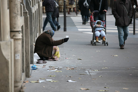 In figure (b), a homeless person, dressed in shabby clothing, is shown sitting on a city sidewalk, holding a plastic cup, begging for change from passers-by.
