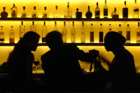 Silhouetted figures in a bar.