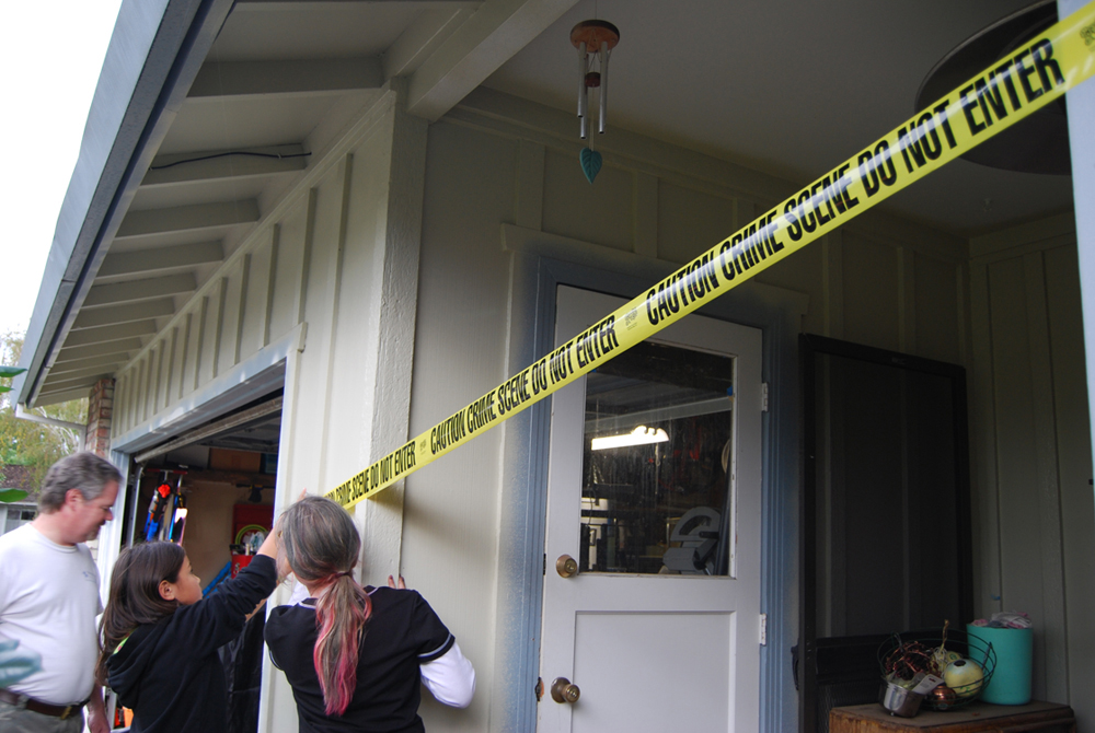 People placing crime scene tape around a house.
