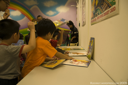 Young students looking at books at a table.