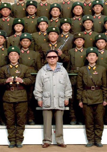Kim Jong-Il of North Korea is shown wearing sunglasses amid a group of uniformed North Korean soldiers.