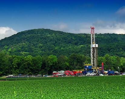 This is a photo of a shale drilling platform below a forested hill.