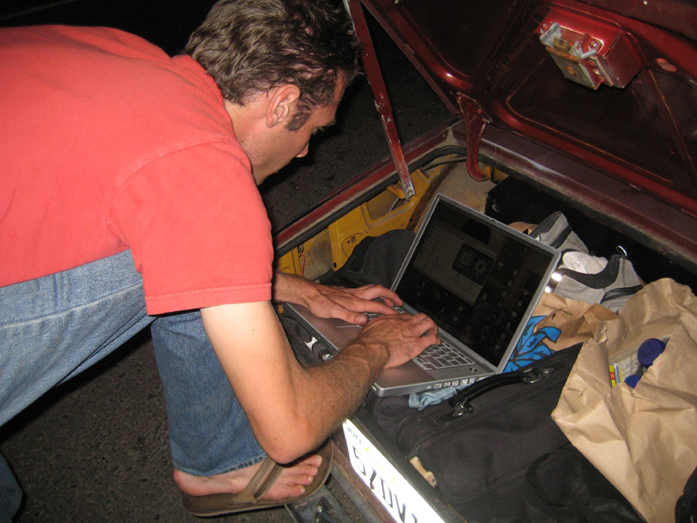 A man leaning over a laptop, typing is pictured here.