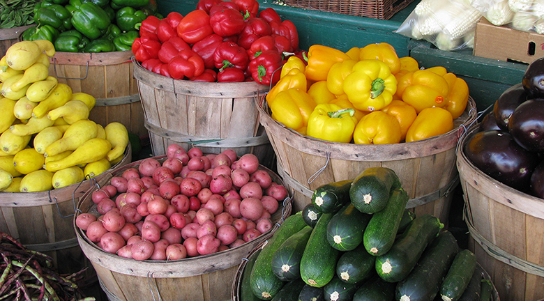 This is a photograph of various organic vegetables in baskets at a farmer's market.