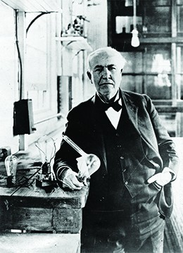 A photograph shows Thomas Edison in a brightly lit workroom. Beside him is a table holding an incandescent light bulb.