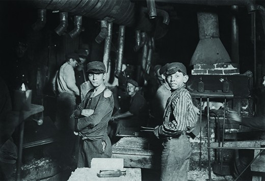 A photograph shows a small group of children working in a factory. Two boys, with tattered clothes and dirt-smudged faces, stand in the forefront.