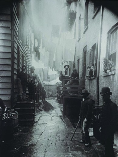 A photograph shows an alley between two tenements. Men, women, and children stand on either side of the alley, in the stoops, and in the windows.