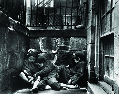 A photograph shows three small children, shabbily dressed and barefoot, asleep in a heap over a steam grate slightly below street level.