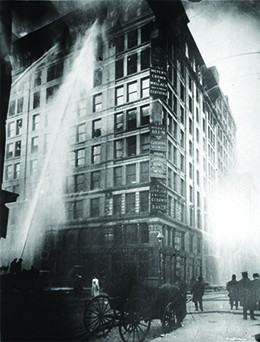 A photograph shows firefighters directing a massive spray of water at the blaze in the Triangle Shirtwaist Factory.
