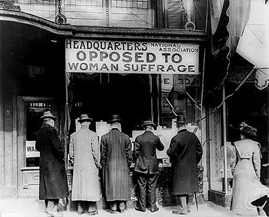 "A photograph shows five men and a woman standing outside of a building labeled ""Headquarters National Association Opposed To Woman Suffrage."""