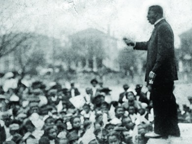 A photograph shows Booker T. Washington speaking and gesturing before a large crowd.