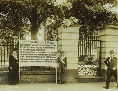 """A photograph shows two suffragists standing in front of the White House gate, holding a large sign between them. The text of the sign reads as follows: """"President Wilson and Envoy Root are deceiving Russia. They say 'We are a democracy. Help us win a world war so that democracies may survive.' We, the women of America tell you that America is not a democracy. Twenty million American Women are denied the right to vote. President Wilson is the chief opponent of their national enfranchisement. Help us make this nation really free. Tell our government that it must liberate its people before it can claim Russia as an ally."""""""