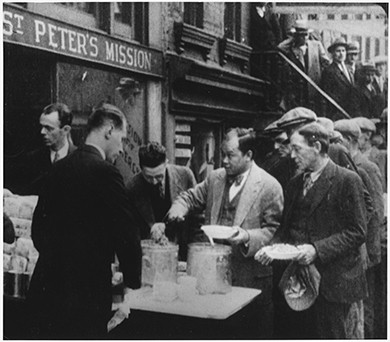 A photograph shows a line of men being served soup in front of St. Peter's Mission in New York City.