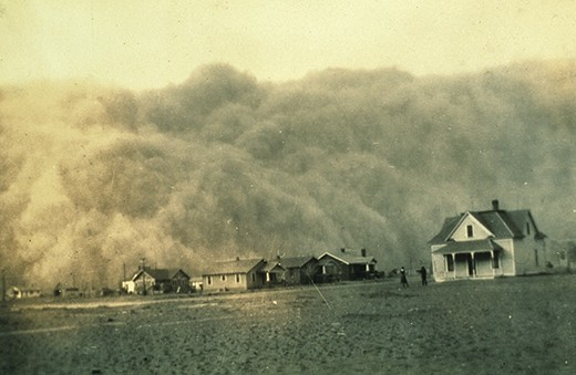 A photograph shows a group of houses on the Great Plains. A massive dust cloud fills the sky overhead.