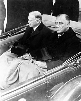 A photograph shows Herbert Hoover and Franklin D. Roosevelt riding side-by-side in the back of a convertible vehicle. A blanket covers their legs, and their hats rest on their laps.