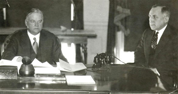 A photograph shows Herbert Hoover seated on the left at a desk with aide Theodore Joselin. The desk contains papers and a telephone. Hoover's facial expression is grim and distracted.