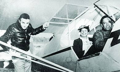 A photograph shows Eleanor Roosevelt smiling from her seat in a two-passenger plane, with an African American pilot in the front. Another African American airman stands beneath the wing.