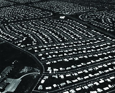 An aerial photograph of Levittown, Pennsylvania shows acres of land with standardized homes in neat rows.