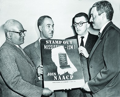 """A photograph shows Henry L. Moon, Roy Wilkins, Herbert Hill, and Thurgood Marshall holding up a poster that reads """"Stamp Out Mississippi-ism! Join NAACP."""" In the middle of the poster, a graphic shows the state of Mississippi with a tombstone in the center. The tombstone displays the names of four African Americans murdered in Mississippi in 1955."""