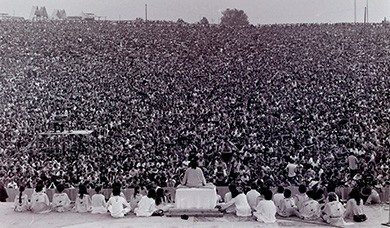 A photograph depicts the rear view of a stage, in front of which a massive crowd is gathered. Swami Satchidananda sits cross-legged atop a podium, with a small group of others seated on the stage to each side of him.