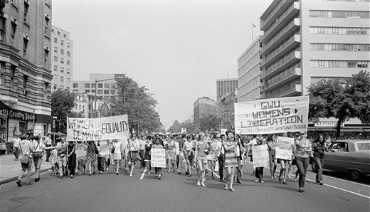 "A photograph shows a protest march of women on a city street. Participants hold signs with messages such as ""Women Demand Equality;"" ""I'm a Second Class Citizen;"" and ""GWU Women's Liberation. Students Employees Faculty Wives Neighbors."""